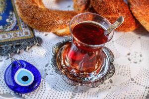 Auf einem gehäkelten Tischuntersetzer liegt ein blaues Nazar-Amulett, daneben ein türkischer Kaffe im Glas, im Hintergrund ein Sesamgebäck und ein Teppich.