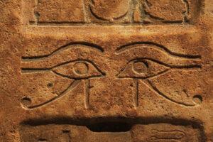 Antike Steinwand mit eingraviertem Ägyptischem Symbol des Horusauges und Auge des Ra