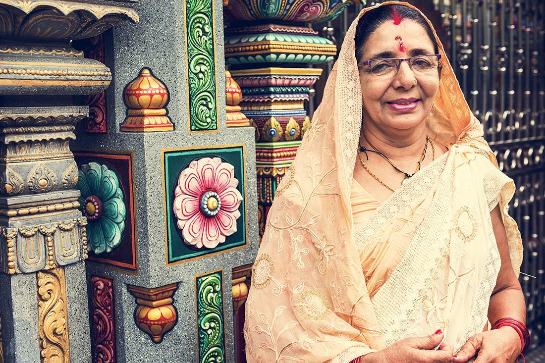 eine indische Frau in tradtioneller Kleidung vor einem Tempel. Auf der Stirn trägt sie den roten Punkt, Bindi.