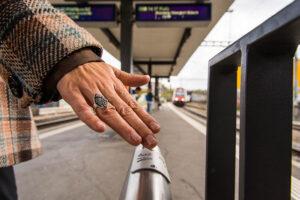 Die rechte Hand einer Frau gleitet über den Handverlauf auf dem Perron eines Schweizer Bahnhofs. Auf dem Handverlauf ist eine gebogene Metallplatte angebracht. Drauf steht in lateinischen Buchstaben 3A sowie auch in Brailleschrift. Im Hintergrund sieht man einen einfahrenden Zug auf dem Gleis.