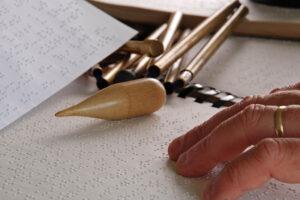 Die linke Hand eines älteren Mannes fährt über die Brailleschrift auf einem Papier. Er trägt einen goldenen Ehering. Ein Hilfsmittel aus Holz mit Spitze sowie kleine Metallstifte liegen ebenso auf dem Ringbuch.