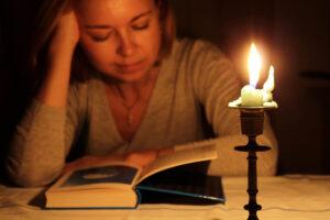 Frau mit langen Haaren sitzt am Tisch, hat ihren Kopf in der einen Hand aufgestützt und liest ein Buch. Vor ihr steht eine brennende Kerze in einem Kerzenständer. Es ist nur das Kerzenlicht als Lichtquelle vorhanden.