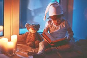 Kleines Mädchen sitzt auf dem Fensterbrett. Draussen ist es dunkel. Sie trägt eine weisse Schlafmütze und ein Pyjama. Sie schaut nach unten in ein Buch. Rechts neben ihr sitzt ein Teddybär und stehen drei Kerzen.