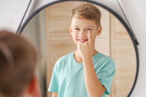 Junge steht vor rundem Spiegel und hat auf dem Zeigefinger eine Kontaktlinse, die er sich vor das Auge hält. Er lächelt und trägt ein hellblaues T-Shirt.