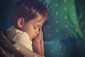 Junger Bub schläft friedlich in der Seitenlage in seinem Bett. Die Hände hat er unter seinem Gesicht. Die Bettdecke und das Kissen sind hellblau mit weissen Sternen.