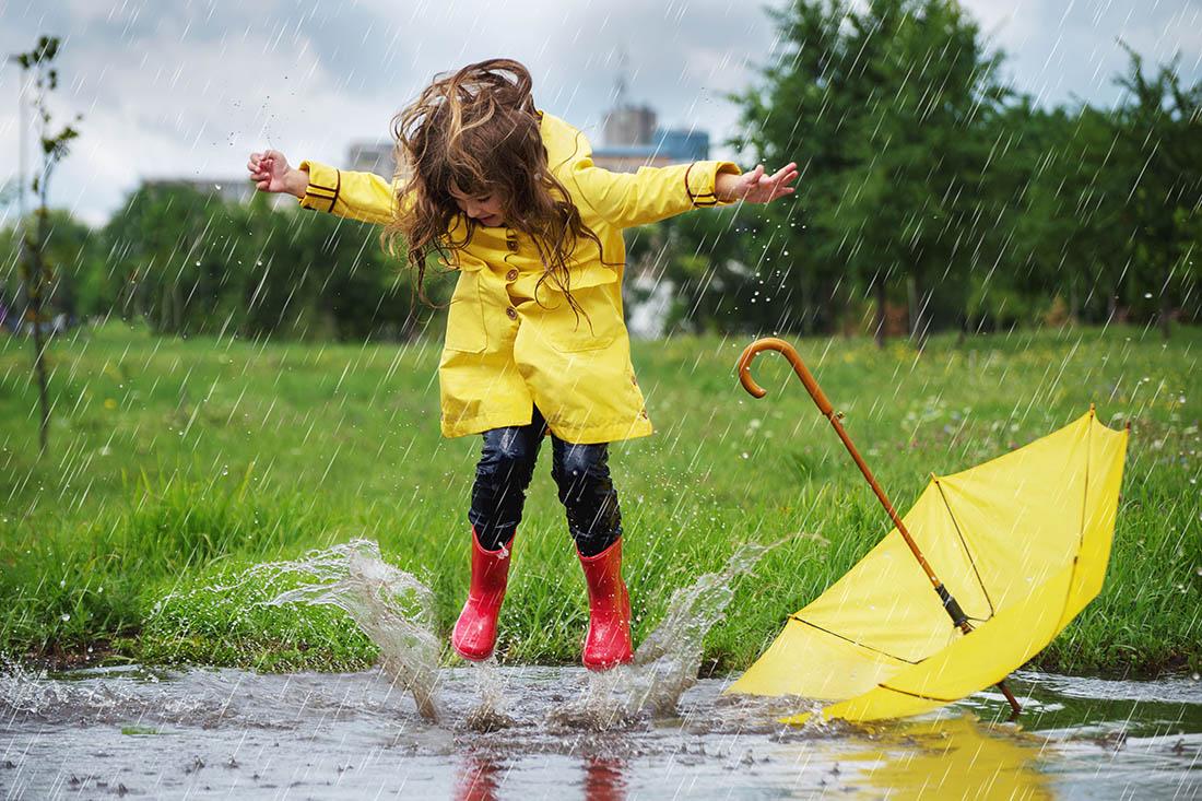 Junges Mädchen mit langen braunen Haaren, gelber Regenjacke, blauen Jeans und roten Regenstiefel springt in eine Regenpfütze. Ein gelber Regenschirm liegt kopfüber neben ihr. Es regnet. Im Hintergrund sind eine Wiese, Bäume und hohe Häuser zu sehen.