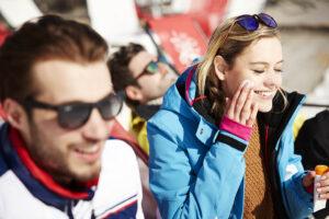Eine Frau und zwei Männer sind in Schneesportkleidung auf Sonnenstühlen. Die Frau cremt ihr Gesicht mit Sonnenschutz ein. Der Mann im Vordergrund trägt eine Sonnenbrille und lacht. Der Mann im Hintergrund liegt im Sonnenstuhl und trägt ebenfalls eine Sonnenbrille.