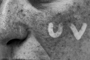 Ultarviolette Fotografie eines Gesichtes. Nahaufnahme einer Wange, auf der UV zu lesen ist.