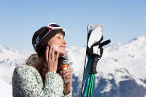 Frau mit Mütze und Skibrille auf dem Kopf cremt sich mit geschlossenen Augen Sonnencreme ein. Die Skier und Stöcke hat sie vor sich hingestellt. Im Hintergrund ist ein schneebedecktes Bergpanorama und blauer Himmel zu sehen.