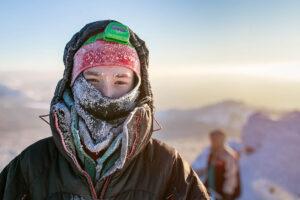 Junger Mann im Winter am Bergwandern, bedeckt mit Mütze, Kapuze und Schal, an denen sich kleine Eiskristalle festgesetzt haben.