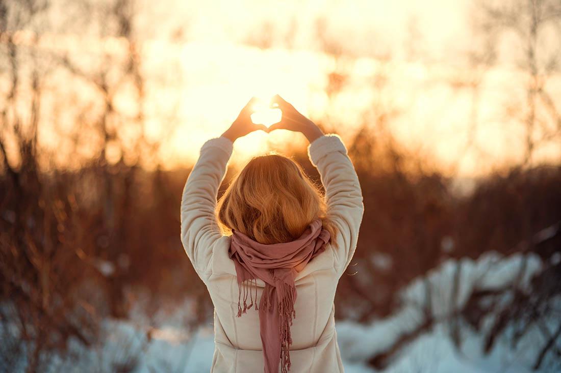 Foto einer Frau in Winterkleidung von hinten in Winterlandschaft, sie formt mit den Händen ein Herz Richtung Sonne.