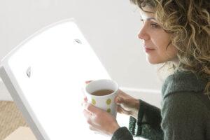 Frau sitzt mit Tee in der Hand vor einer Lichttherapielampe.