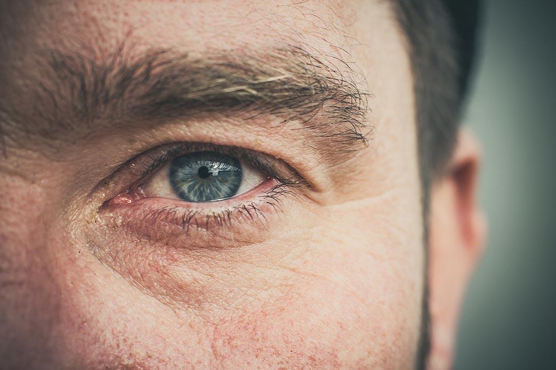 Nahaufnahme einer Gesichtshälfte eines Mannes mit buschigen Augenbrauen und Wimpern.