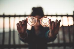 Eine Brille mit in den Staub gezeichneten Herzen auf beiden Gläsern wird von junger Frau in die Kamera gehalten.