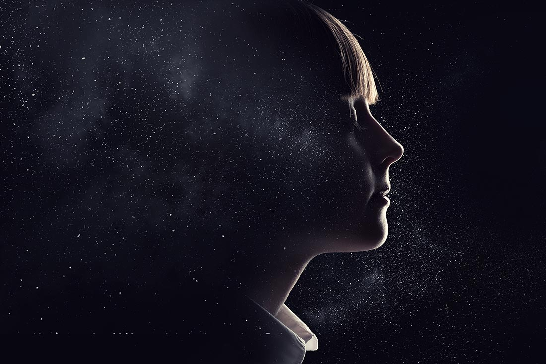 Hell beleuchtetes Profil eines Mädchens geht über in dunklen Sternenhimmel.