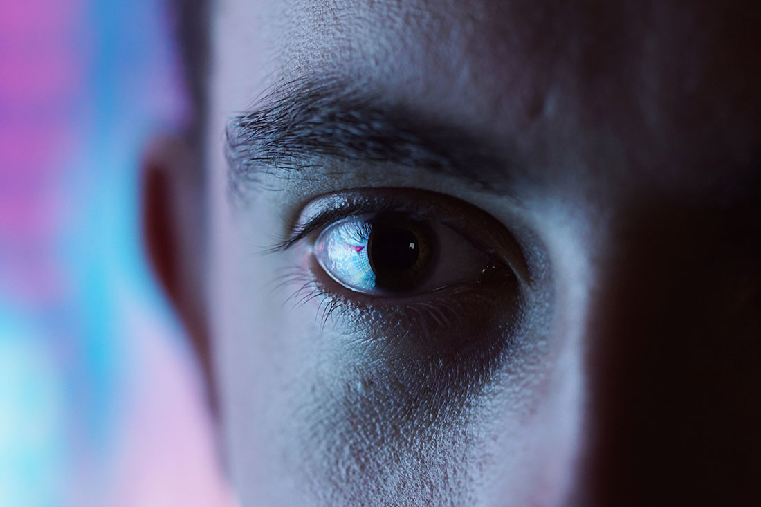 Ausschnitt einer Fotografie eines männlichen Gesichts, dessen eine Hälfte im Dunkeln liegt. Verschwommener Hintergrund in Blau- und Violetttönen.