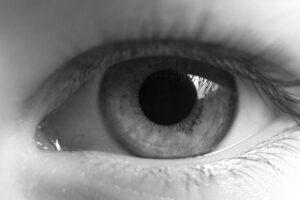 Nahaufnahme eines Auges mit erweiterter Pupille in schwarz weiss.