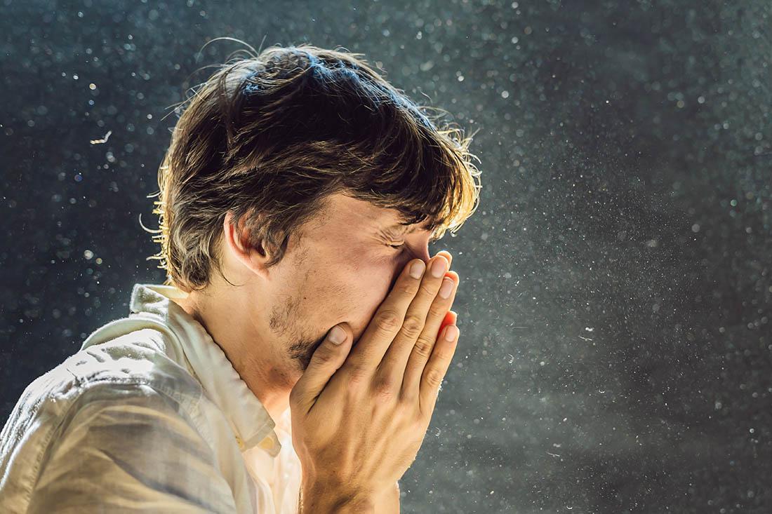 Mann umgeben von Staub in der Luft niest in die Hände.