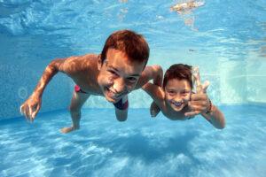 Zwei Jungen tauchen in einem Swimmingpool mit geöffneten Augen. Die Kinder werden frontal von vorne gezeigt, man sieht die leicht geröteten Augen.