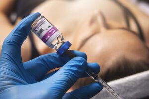 Eine Botox-Spritze wird vorbereitet, im Hintergrund liegt wartend eine Frau.