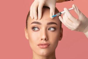 Eine jungen Frau bekommt eine Botox-Sprite in die Stirn.