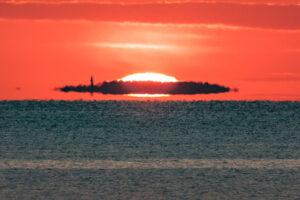 Am Horizont auf dem Meer bildet sich eine Fata Morgana, die aussieht, als würde ein Mann ein fliegendes Geisterschiff steuern.