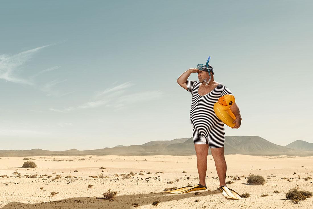 Ein Mann mit Badeanzug und Quietscheente steht alleine in der Wüste und hält Ausschau nach Wasser.