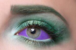 Das geschminkte Frau einer Auge ist lila tätowiert.