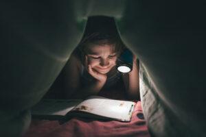 Ein Mädchen liest unter der Bettdecke mit einer Taschenlampe ein Buch.