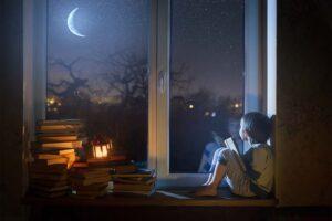 Ein Kind liest nachts auf dem Fensterbrett ein Buch.