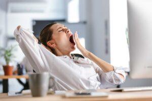 Eine Frau gähnt herzhaft am Arbeitsplatz.