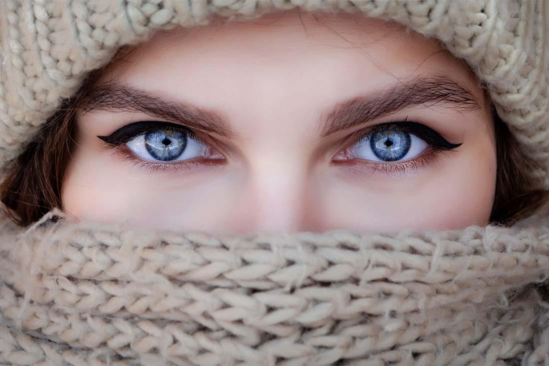 Die blauen Augen einer Frau sind fokussiert, der Rest ihres Gesichts ist hinter Schal und Mütze versteckt.