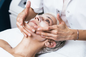 Eine Frau wird von Fachpersonal mit chemischem Peeling im Gesicht eingerieben.
