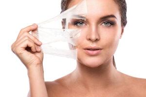 Eine Frau zieht sich die Peeling-Maske vom Gesicht wie eine zweite Haut.