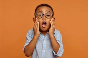 Ein kleiner Junge mit Brille blickt dramatisch in die Kamera.
