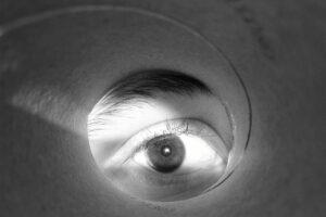 Ein Auge schaut durch ein aufgerolltes Papier hindurch wie durch ein Fernrohr.