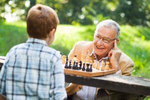 Ein alter Mann mit Brille spielt mit einem Jungen Schach.