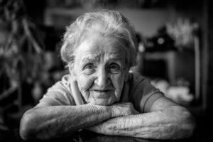 Eine alte Frau blickt freundlich in die Kamera.