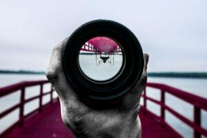 Jemand hält ein Sichtrohr vor die Kameralinse, durch das der Steg am Wasser kopfüber erscheint.