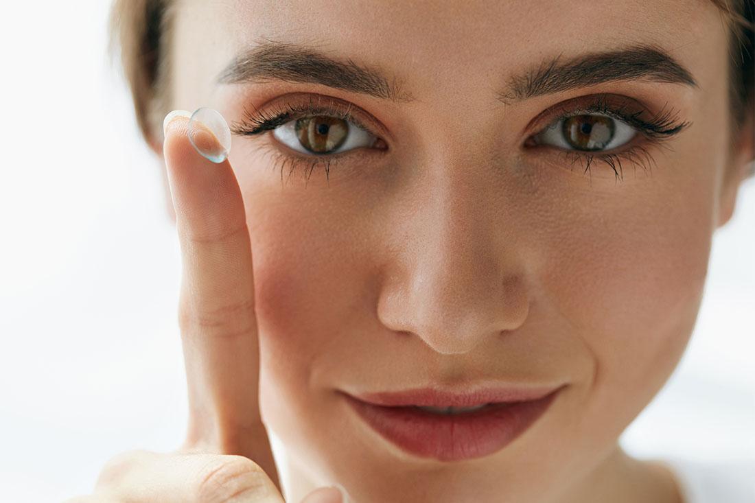 Eine geschminkte Frau hält mit einem Finger eine Kontaktlinse zur Kamera.