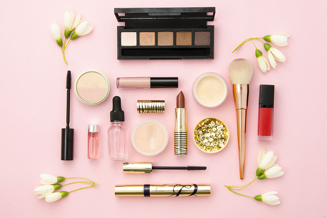 Verschiedene Make-Up-Produkte liegen auf einem rosa Tisch verteilt.