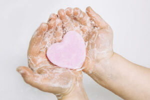 Eine Person hält eine rosa Seife in Form eines Herzens in der Hand.