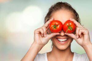 Eine Frau hält zwei rote Tomaten vor die Augen.