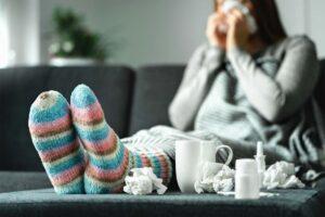 Eine Frau sitzt naseputzend auf dem Sofa, im Vordergrund sind Taschentücher und eine Teetasse.