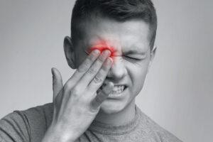 Ein Mann fasst sich schmerzerfüllt ans Auge, dass durch Bildbearbeitung rot erleuchtet ist.