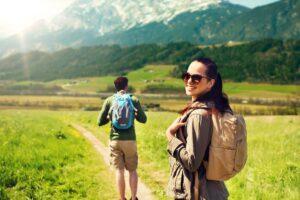 Eine Frau wandert mit Sonnenbrille in die Berge.