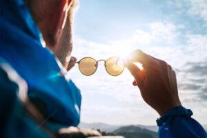 Ein Mann hält seine Sonnenbrille gegen die Sonne.