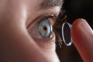 Eine Person setzt sich eine Kontaktlinse ins Auge.
