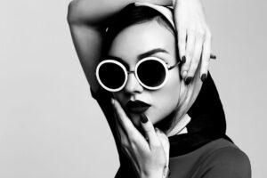 Schwarz-Weiß-Bild einer Frau, die eine eine auffällig große Retro-Sonnenbrille trägt.