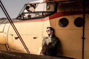 Ein Pilot sitzt mit Flieger-Sonnenbrille vor dem kleinen Flieger.
